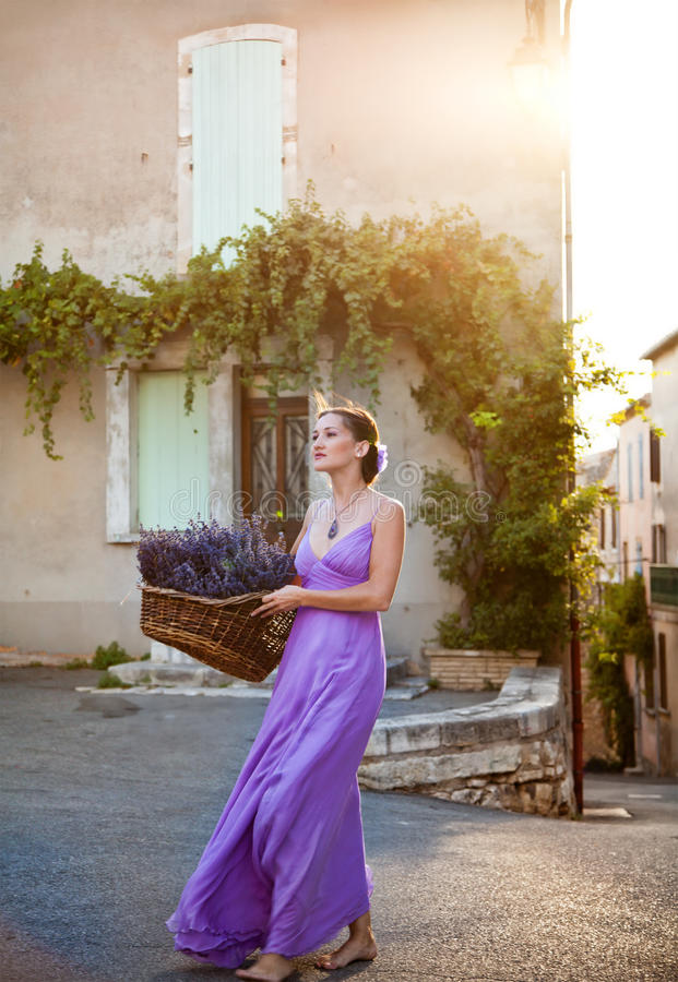 有新近地被切的淡紫色篮子的女孩在老城市 图库摄影