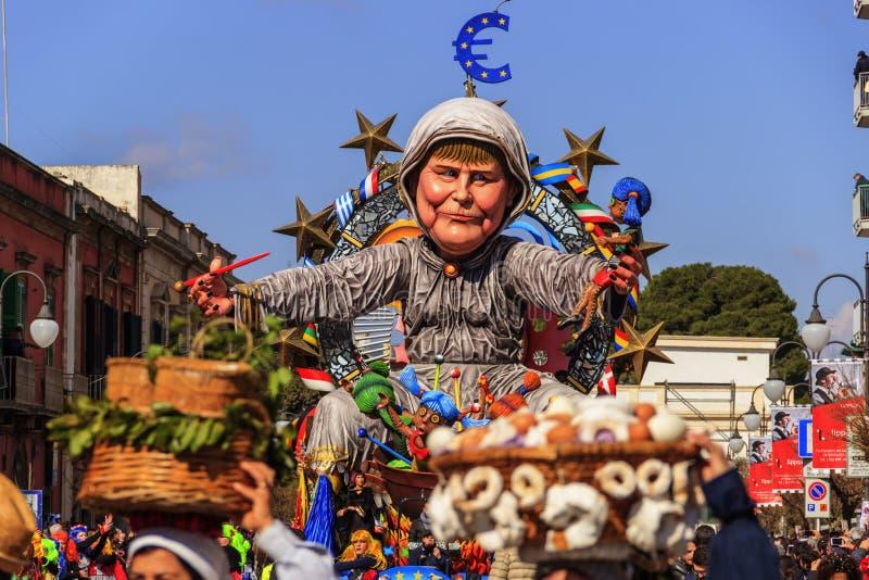 普蒂尼亚诺狂欢节:浮游物 欧洲政客:安格拉・默克尔酷刑欧洲 意大利(普利亚) 库存照片