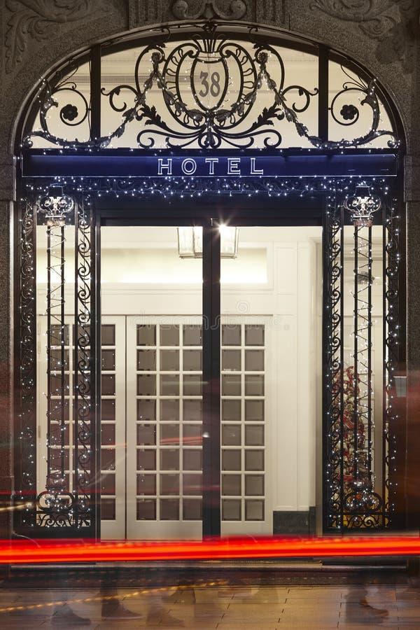 普通旅馆门面在与城市光和街道的夜之前 免版税图库摄影