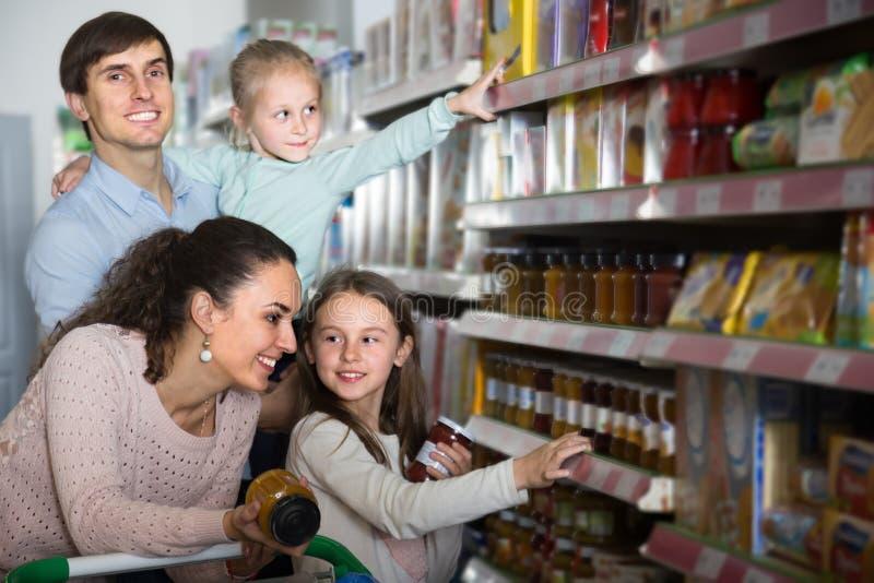 普通的年轻家庭画象在地方超级市场 库存图片