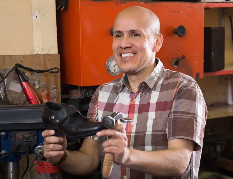 普通的资深在针车床的工作员缝合的皮靴 图库摄影