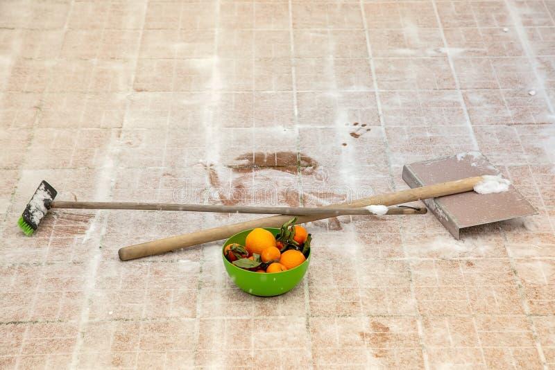普通话和桔子在绿色碗 很好工作的维生素Ð ¡ 工作的能量 铁铁锹和笤帚有木把柄的 库存照片