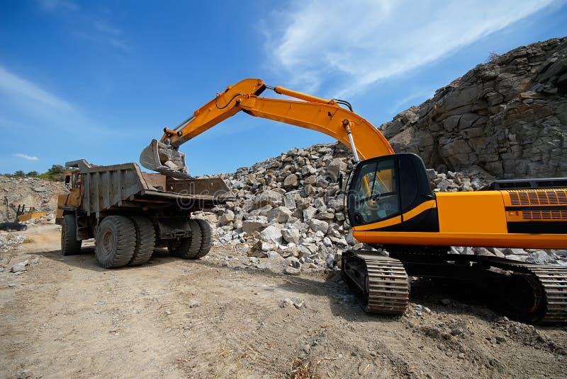 普遍挖掘机在倾销者装载花岗岩石头 免版税库存照片