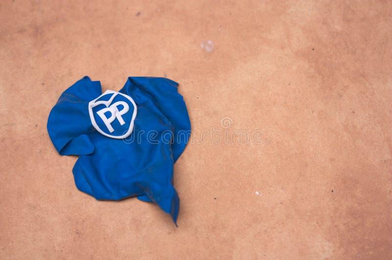 普遍的西班牙党的一个残破的增进气球在地面上的 库存照片
