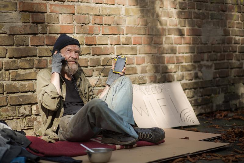 晴天,从太阳能电池的无家可归的老人充电的电话 库存图片