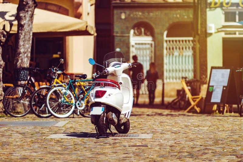 晴朗的假日在老城市,在街道上的大黄蜂类滑行车 免版税库存照片