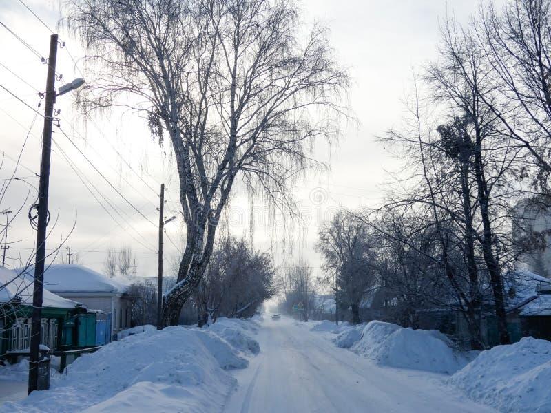 晴朗的冬日在西伯利亚 去天际,全部的狭窄的街道雪  库存照片