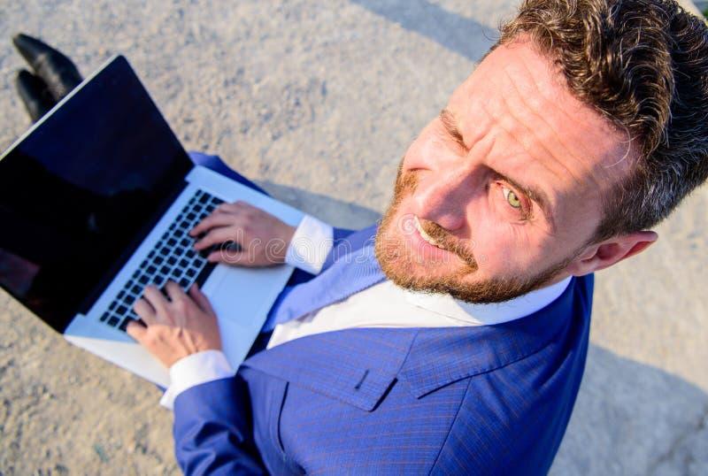 晴朗的夏日重要机遇工作外面 人微笑的快乐的面孔与膝上型计算机关闭一起使用 商人 免版税库存照片