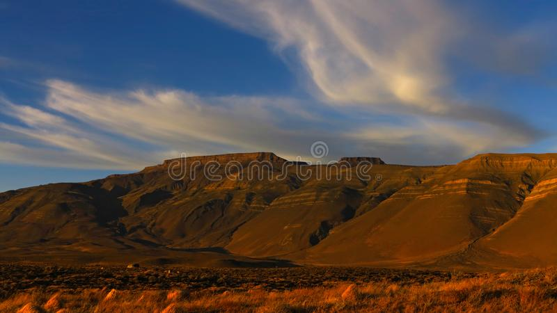 晴朗的山 在山顶的风吹的云彩 蓝天 免版税库存图片