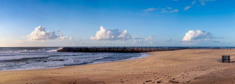 晴蓝多云的天空下,白天空的大滩 库存图片