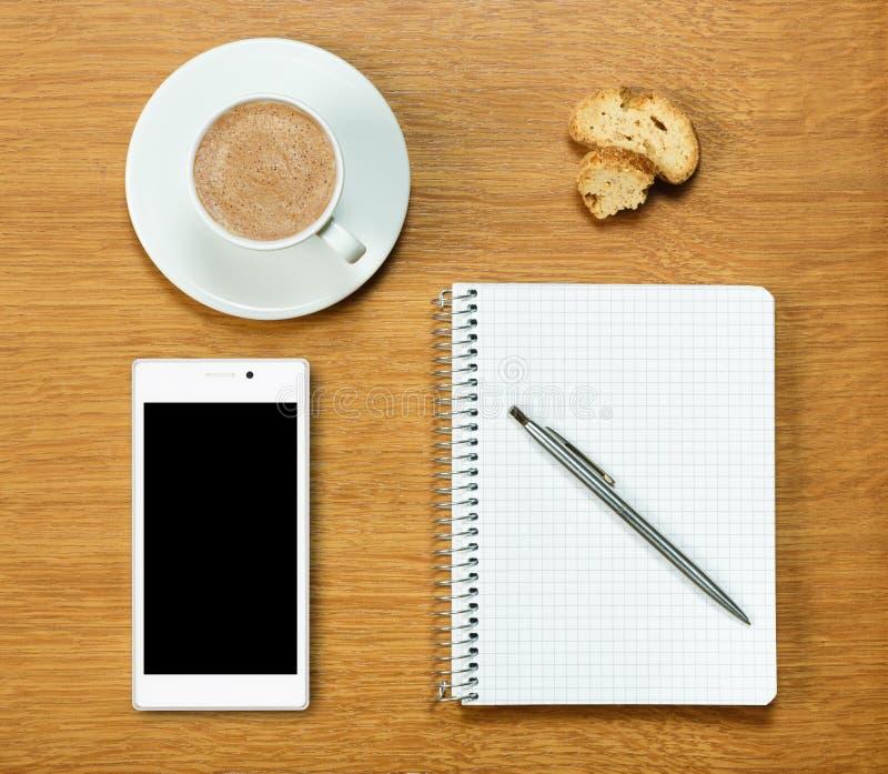 智能手机、咖啡、笔记薄和笔 库存照片