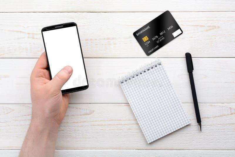 智能手机、笔记本、笔和信用卡在一张白色桌上 库存照片
