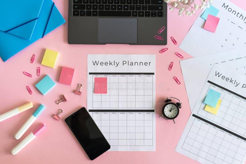 智能手机、膝上型计算机、文具和计划者桃红色淡色背景的 免版税库存照片