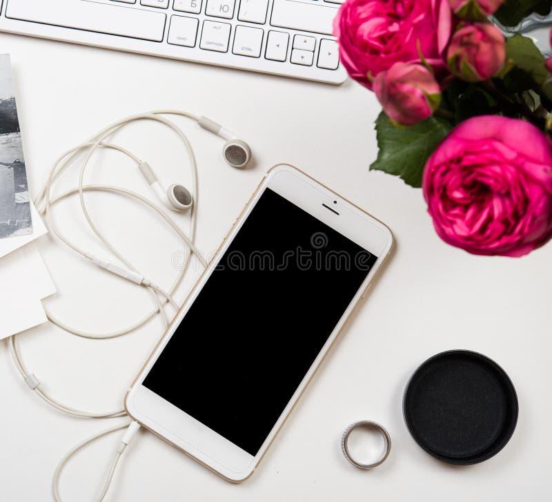 智能手机、键盘和fesh桃红色花在白色选项 库存照片