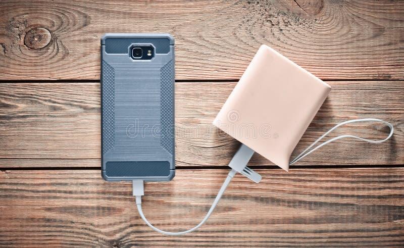 智能手机从力量银行被充电在一张木桌 现代的小配件 免版税库存照片