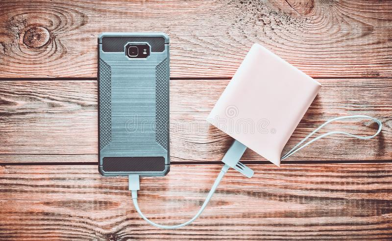 智能手机从力量银行被充电在一张木桌 图库摄影