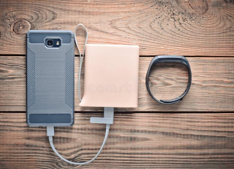 智能手机从力量银行,在一张木桌上的巧妙的镯子被充电 现代的小配件 免版税库存图片