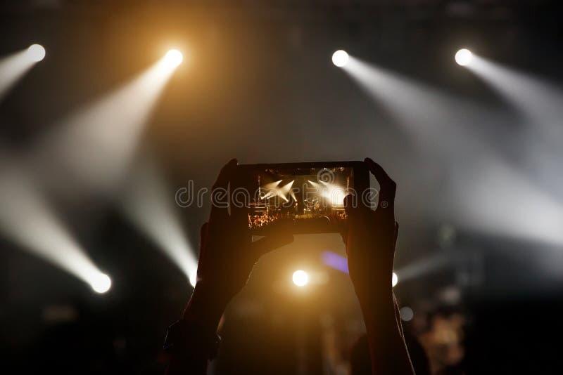 智能手机剪影在妇女的手上音乐会展示的 库存图片