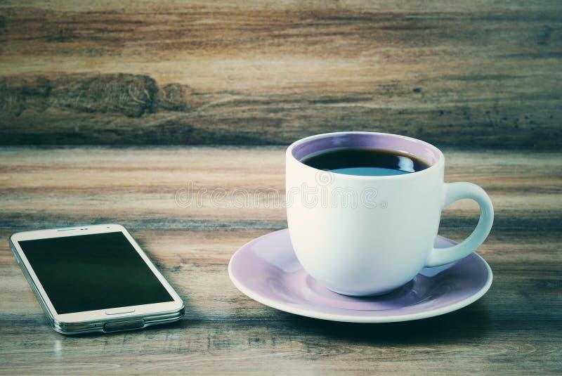 智能手机和一杯咖啡葡萄酒样式 免版税库存照片