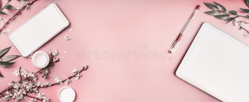 智能手机和平板电脑嘲笑在与化妆用品、文具supples和白色开花分支的粉红彩笔桌面背景, 库存图片