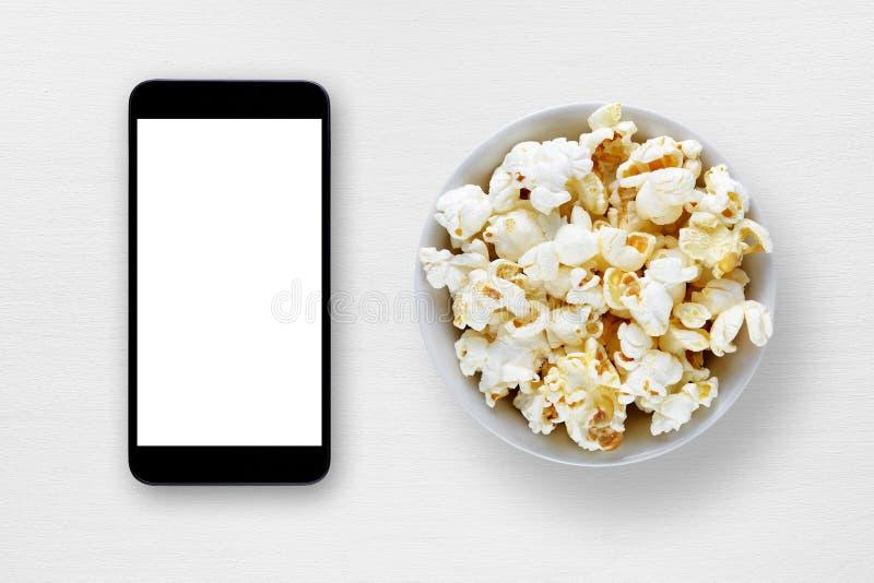 智能手机和玉米花在碗在桌上 图库摄影