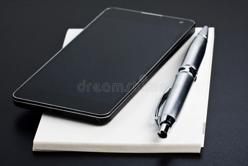 智能手机和笔在备忘录书 免版税库存照片