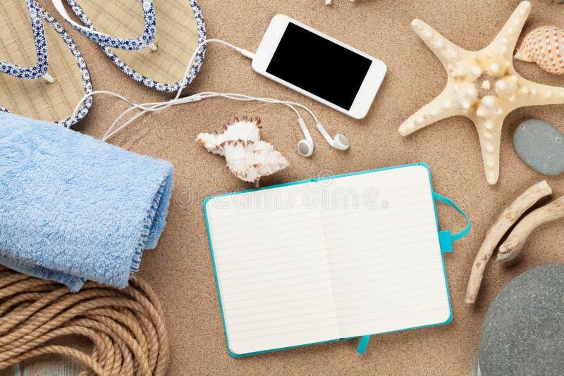 智能手机和笔记薄在海沙与海星和壳 免版税库存照片