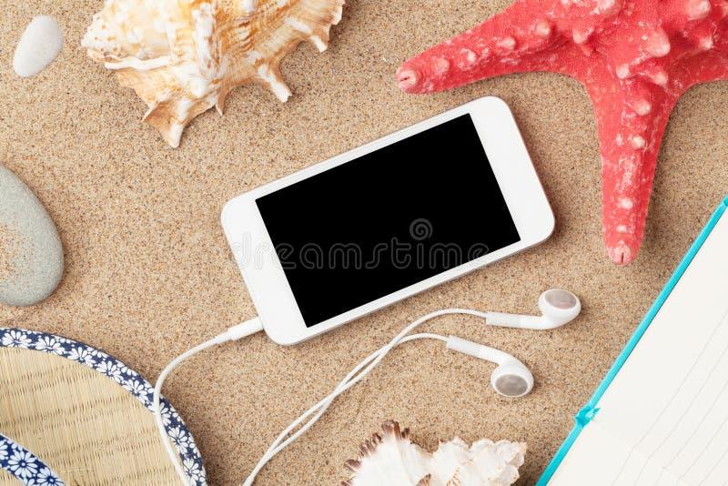 智能手机和笔记薄在海沙与海星和壳 免版税库存图片