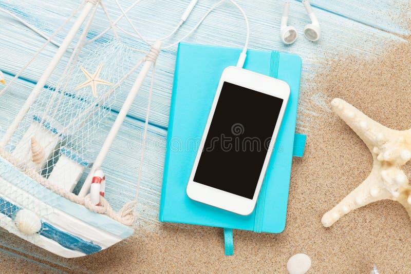 智能手机和笔记薄在海沙与海星和玩具小船 免版税图库摄影