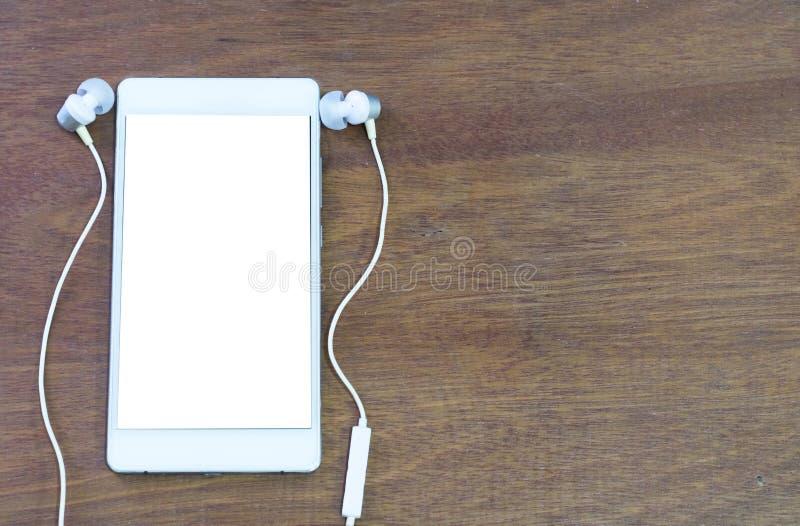 智能手机和耳机在木背景与拷贝空间 库存照片