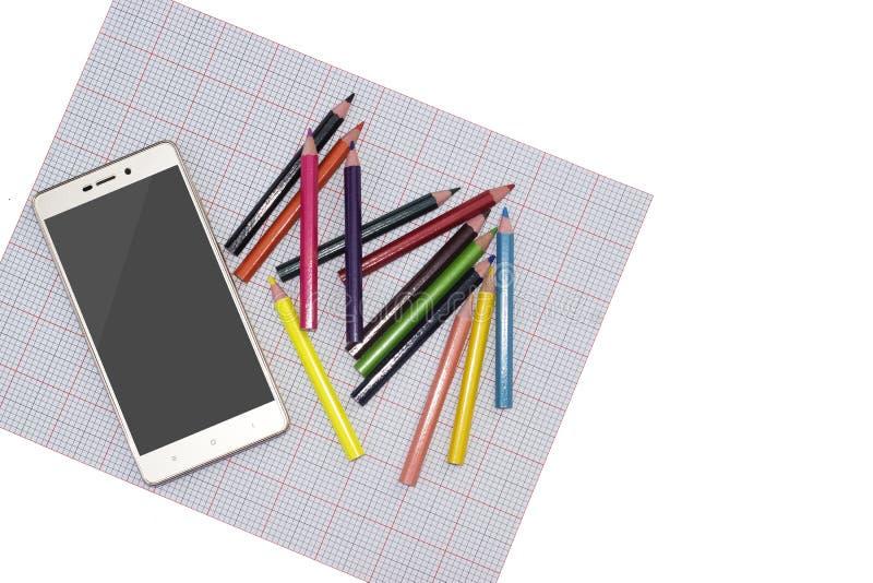 智能手机和色的铅笔在一张轻的背景侧视图 样品的嘲笑 免版税库存图片