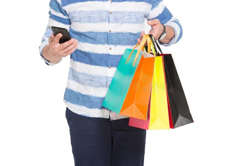智能手机和购物袋在买家的手上 与电话的网上购物 Uptoday机动性商务 电子商务打折销售 库存照片