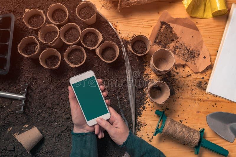 智能手机嘲笑在有机花匠的手上 库存照片