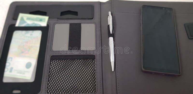 智能手机在与笔和塞尔维亚纸币的开放皮革文件夹放置 免版税库存照片