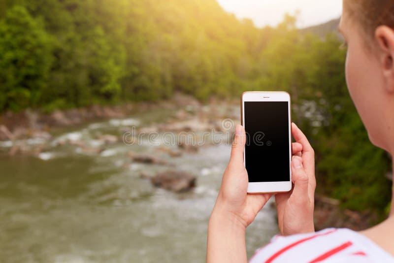 智能手机在妇女的手,摄影师上做照片美好的自然,在设备的黑屏 山河照片和 库存照片
