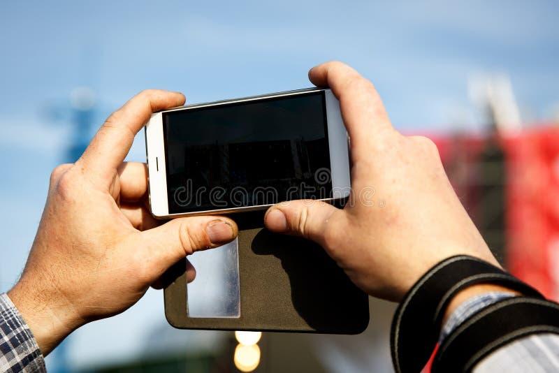 智能手机在手中 拍摄在夏天音乐节 免版税库存照片