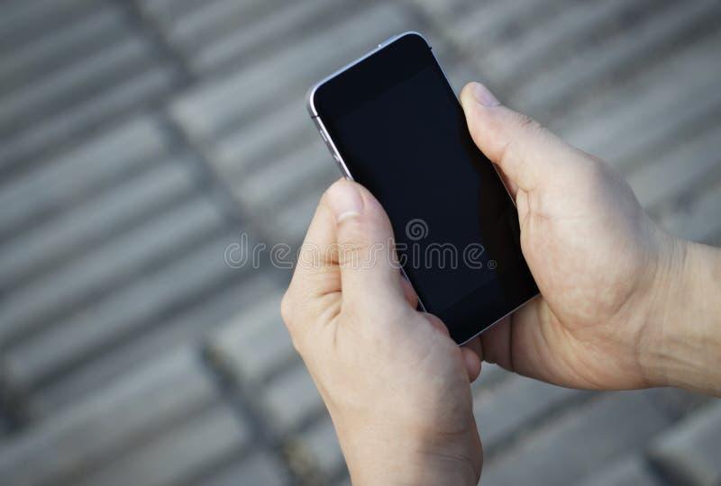 智能手机在男性手上,顶视图,户外 免版税图库摄影