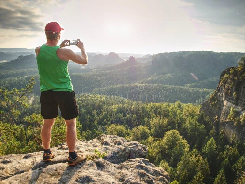 智能手机摄影师 岩石边缘作为电话图片的游人 人由巧妙的电话拍风景照片 库存照片
