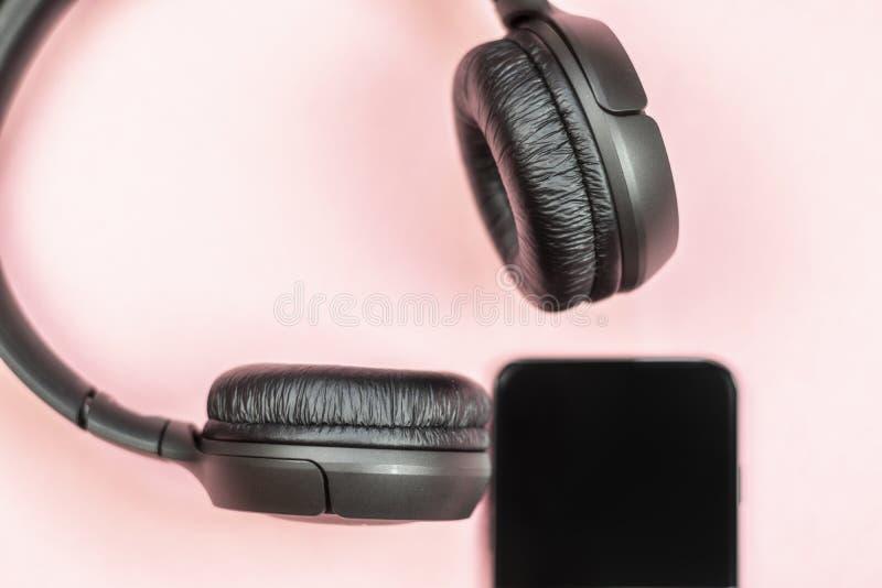 智能手机特写镜头有耳机的在桃红色背景 免版税库存照片