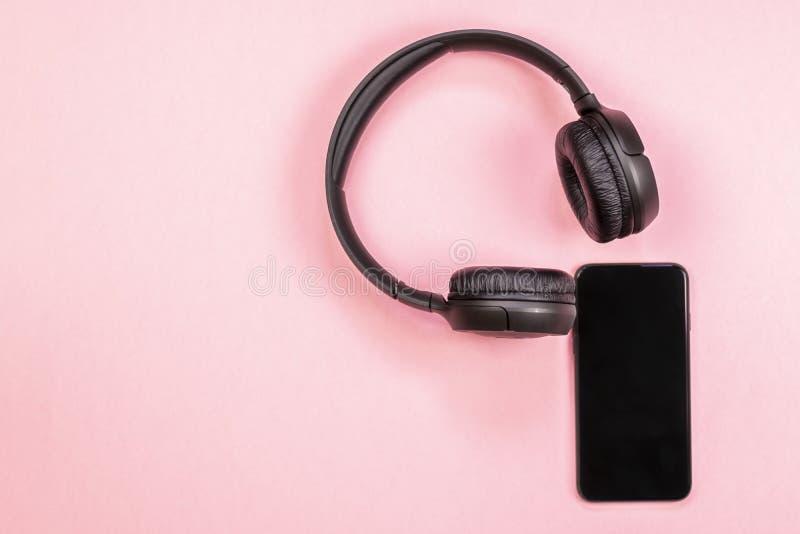 智能手机特写镜头有耳机的在桃红色背景 图库摄影
