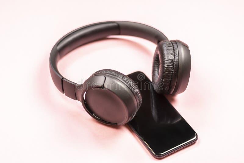 智能手机特写镜头有耳机的在桃红色背景 库存照片