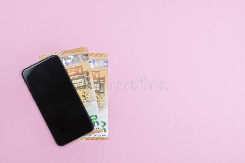 智能手机特写镜头有金钱的在桃红色背景 库存图片