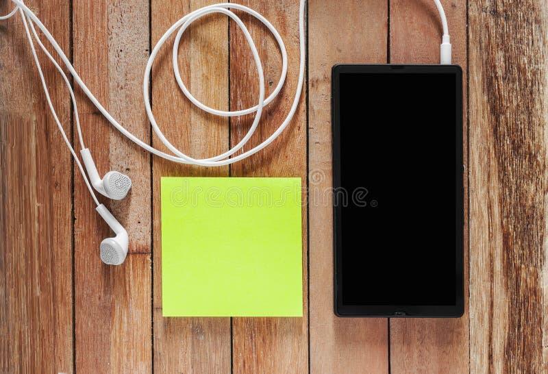 黑智能手机特写镜头有耳机和稠粘的笔记的 免版税库存照片