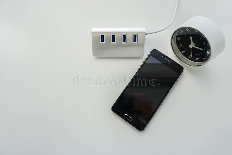 智能手机电池充电的USB插孔与被环绕的现代时钟 免版税库存图片