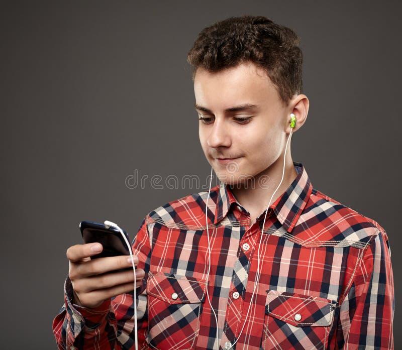 从智能手机的青少年的听的音乐 免版税库存图片