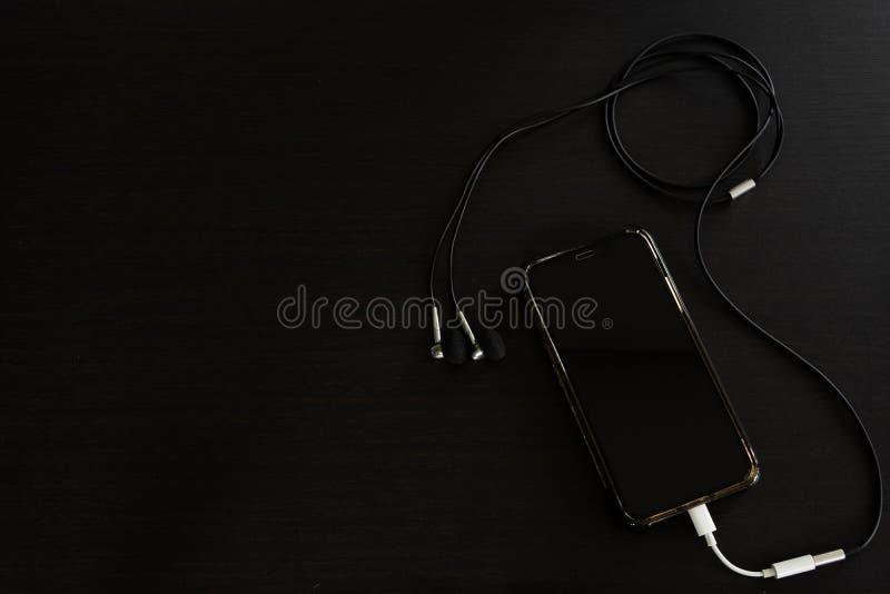 智能手机,与耳机的iPhone x,在黑木桌上 免版税库存图片
