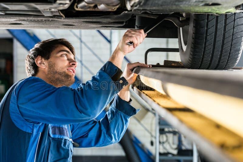从暂停的汽车的技工改变的轮胎在汽车商店 库存照片