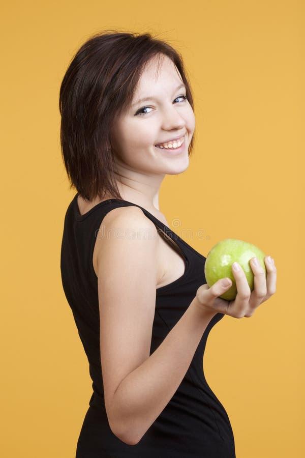 暂挂一绿色苹果微笑的十几岁的女孩 免版税库存图片