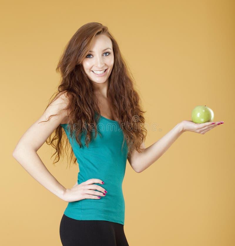 暂挂一绿色苹果微笑的女孩 免版税库存照片