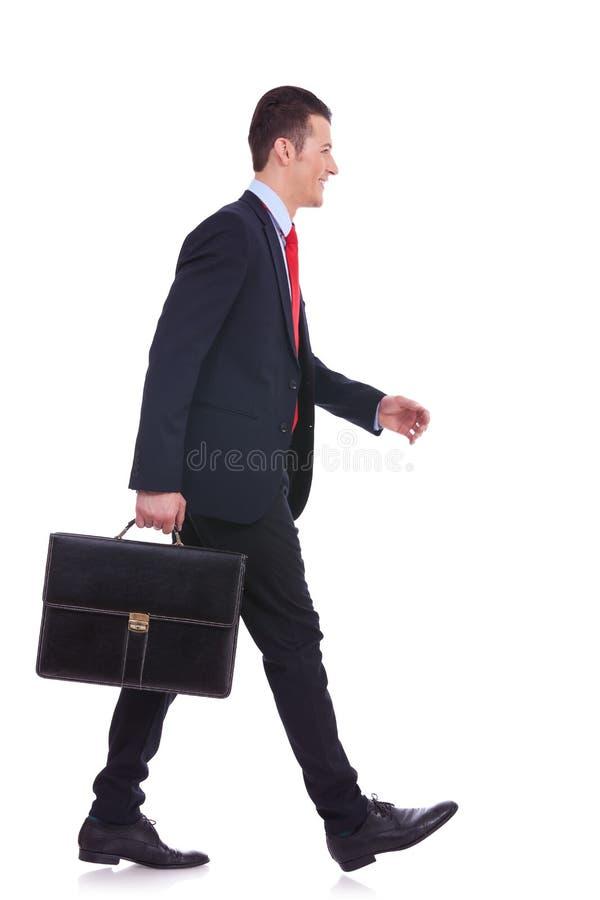 暂挂公事包和走的商人 库存图片